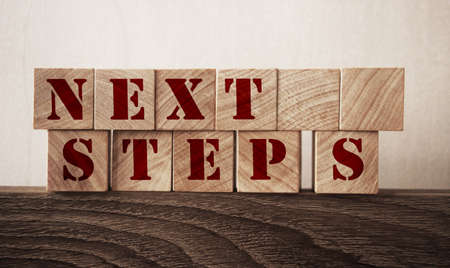 Next Steps written on a wooden cubes in a office desk. Education and business startup concept.