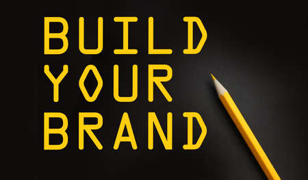 BUILD YOUR BRAND words on black with yellow pencil besides. Branding rebranding marketing business startup concept.