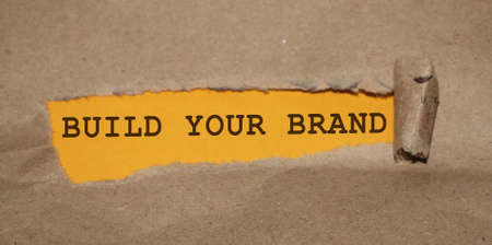 BUILD YOUR BRAND message written under torn paper. Branding rebranding marketing business concept.