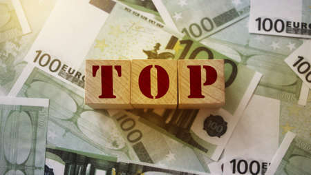TOP word on wooden cubes blocks pur on money 100 Euro banknotes. Top management big salary career concept. Banco de Imagens