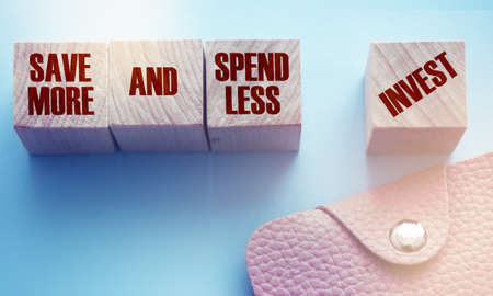 Save More and Spend Less Invest on wooden cubes and pink leather wallet. Investment and saving money financial concept.