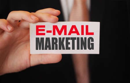 Email marketing words on card a businessman shows. Bsuiness strategy client oriented concept.
