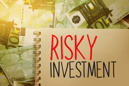 Risky investment words written on copybook page. Saving and invest financila business concept