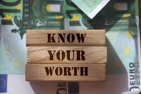 Know Your Worth on wooden blocks pur on 100 Euro banknotes. High salary big wages high qualification concept.