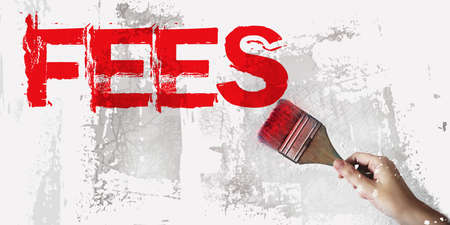 Fees word in red and brush in hand on grundge white grey background. Taxes and fees concept. Foto de archivo