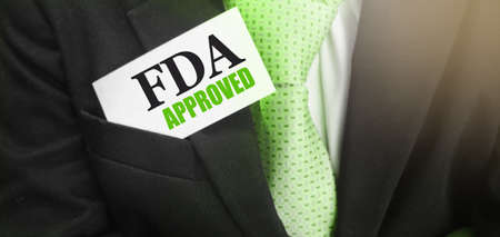 FDA Approved words on card in upper pochet of businessman suit. Food and Drugs Association approved products concept.