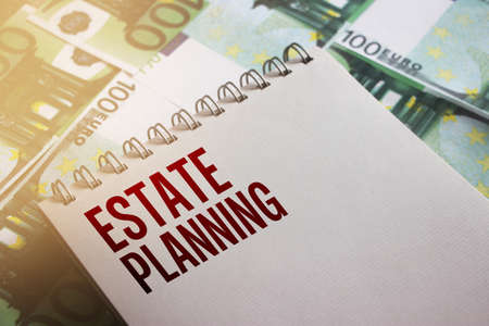 Estate Planning written on page of copybook put on 100 Euro banknotes. Real estate bent and buy business concept.