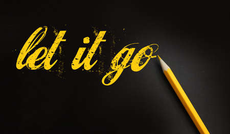 Let it go words written with a yellow pencil on black. Forgiveness, future planning and new life beginning concept.