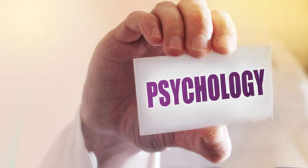 Psychology word written on a card in doctor's hand. Antistress therapy healthcare concept.