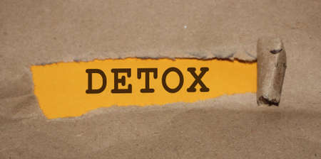 Detox word written under torn paper. Healthcare healthy diet fighting addictions concept .
