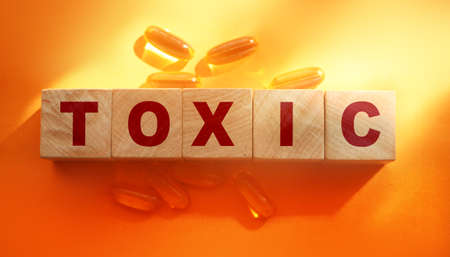 Toxic Word written on wooden cubes with Omega-3 pills around. Detoxification healthcare concept.