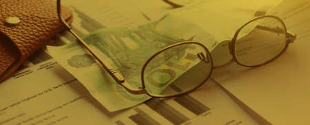 Leather wallet, euro banknote and glasses pur on agreement, toned into soft yellow. Vintage style. Business contract concept. Banque d'images