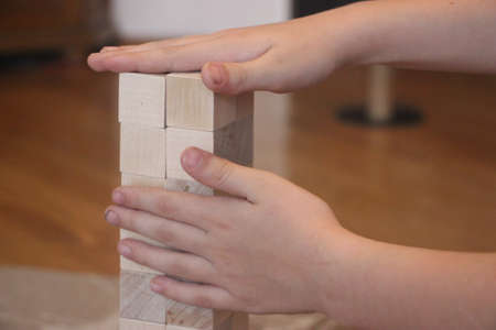 Hands establishes a wooden cubes construction. Business startup concept.