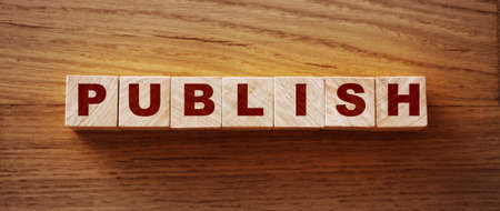 Publish written on a wooden cube on a wood desk. Publishing news concept.