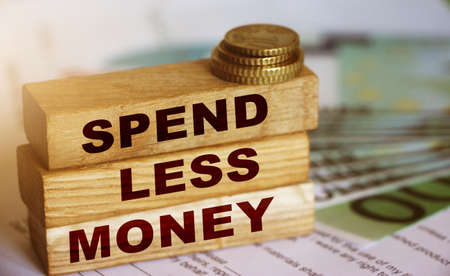 Spend Less Money on wooden block, 100 Euro currency bills and coins. Financial concept. Selective focus.
