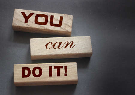 YOU CAN DO IT word on wooden blocks on gray background. Motivation affirmation encouraging words for personal achievements concept.