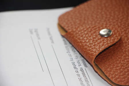 Wallet made of brown natural leather pur on Agreement or contract. Business concept.