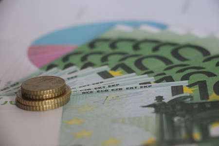 Stack of euro coins put on 100 euro banknotes. with financial report graph in the form of pie diagram. Financial business concept. 写真素材
