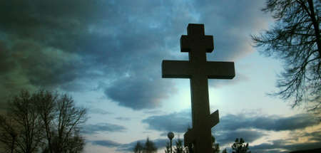 Cross in cemetry in evening under stormy sky. Life and death concept.