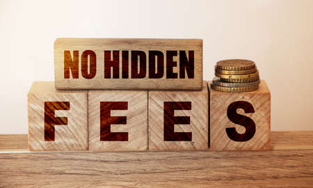 No hidden fees word written on wood blocks and pill of coins. Business agreement transparency and honesty concept.