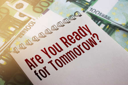 Are you ready for tommorow words on page of copybook put on 100 Euro banknotes. Financial saving and investment risk management future planning business concept.