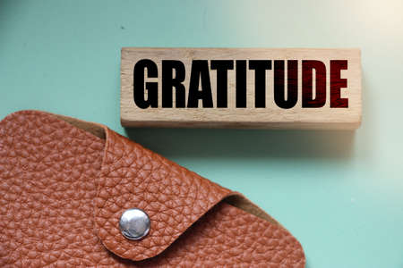 Gratitude word on wooden block and leather wallet. Donation charity foundation fundraising business concept. Banque d'images