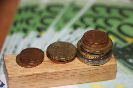 3 Stacks of coins on wooden block put on many 100 Euro bills background. Money, currency and business growth concept. Фото со стока