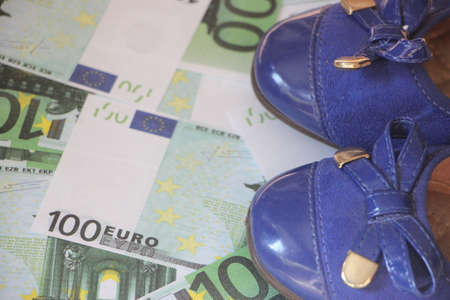 Woman's blue ballet Shoes stepped on the money 100 Euro bills. Money wasting and spending concept. Stock Photo