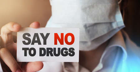 Doctor holding a card with Say no to drugs, Medical drugs addiction prevention awareness healthcare concept