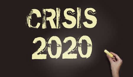 Crisis 2020 text on a chalk board. An economic and financial crisis is coming due to the prevailing coronavirus around the world. Stock Photo