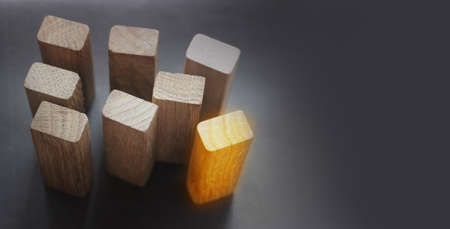 7 same and 1 different wooden blocks standing on black background. Leadership and team abstract business concept.
