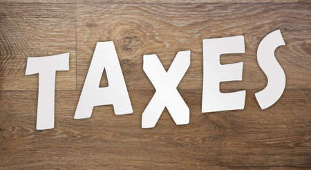 Taxes word letters cut from white paper on wooden background. Taxes, fees and penalties business concept.