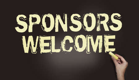Sponsors welcome phrase handwritten on chalkboard with chalk in a hand. Business startup concept.