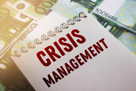 Crisis management words on page of copybook put on 100 Euro banknotes. Business risks and failures concept. Selective focus. Foto de archivo