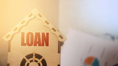 LOAN word on a small wooden toy house. Real estate loan social program or business project concept. Banque d'images