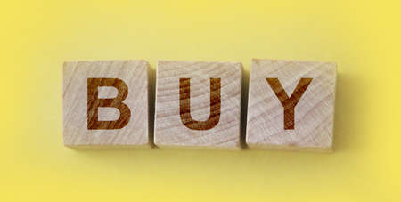 Shopping concept. Wooden cubes with word buy on the yellow background .