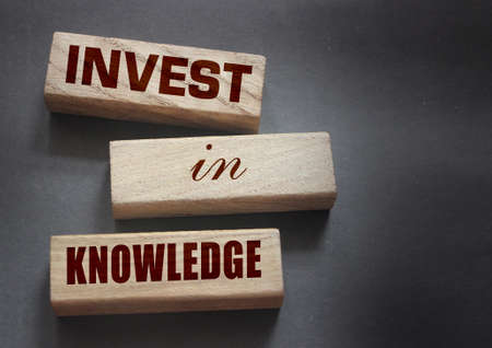 Invest in knowledge words onwooden blocks. Inspirational motivational quote. Investment in knowledge pays the best dividends, education or business training concept.