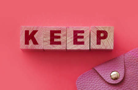 Keep word on wooden blocks and leather wallet. Saving things as they are. Save money concept.