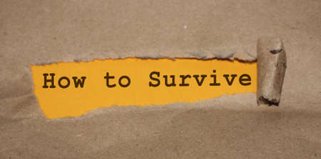 How to survive words written under torn paper. Surviving in crisis business concept.
