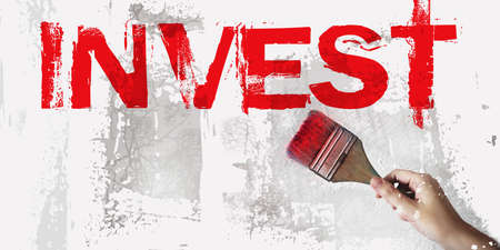 Old grunge paintbrush painting red word Invest on grey wall. Investment saving money financial assets concept. 写真素材