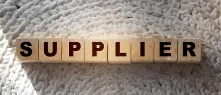 SUPPLIER word n wooden cubes on crochet carpet. Textile production manufacture business concept.