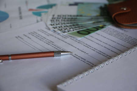 Many hundred Euro banknotes, leather wallet and a pen on agreement. Business desicion concept.