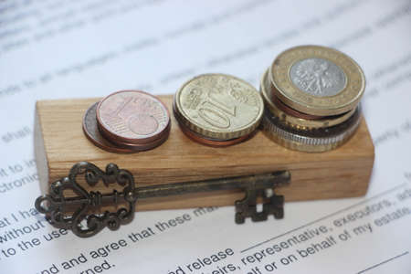 Stacks of coins like growing diagram put on stamp on agreement and vintage key. Business growth financial profit concept. Key to success.