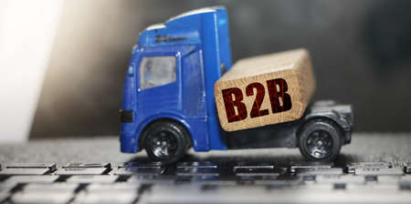 Toy truck moves a pallet with wooden block with B2B abbreviation. depicts delivering goods or products around globe in e-Commerce. Business to Business concept. Logistic network distribution and cargo freight concept.