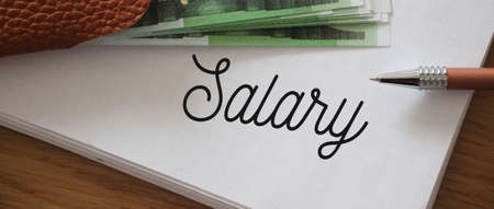 Salary word and some 100 Euro banknotes on copybook page. Employment looking for work concept, career concept.