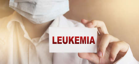Doctor holding leukemia card in hands. Healthcare medical concept. Stock Photo