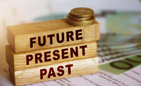 Past Present Future words written on wood block. 100 Euro banknotes and coins. Investment and saving for future planning career and retirement concept. Фото со стока