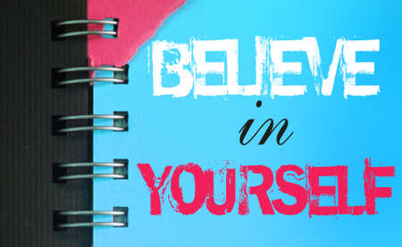Believe in Yourself text message words on sky blue page of copyybok in white and pink. Startup Motivational Business Inspirational concept.