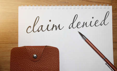 Claim Denied words on copybook page, a pen and leather wallet on wooden table. Business sponsorship or insurance payment reject concept. Foto de archivo