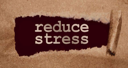Torn brown paper on dark red surface with Reduce Stress words.